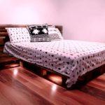 кровать из поддонов с черно-белой постелью