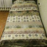кровать из поддонов с зелным покрывалом