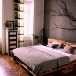 кровать из поддонов с веткой на стене