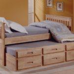 высокая деревянная кровать с выдвижными ящиками
