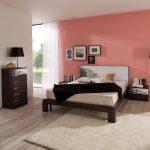кровать с розовой стеной