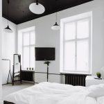 просторная спальня с темной мебелью и белыми стенами