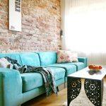 синий диван с кирпичной стеной