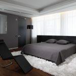 темная мебель в спальне с большим окном
