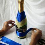 процесс украшения бутылки лентой